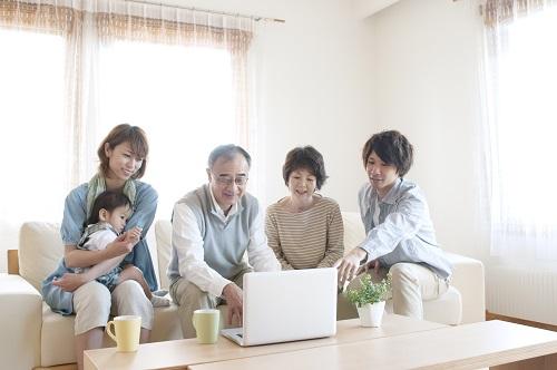 ノートパソコンを見る3世代家族